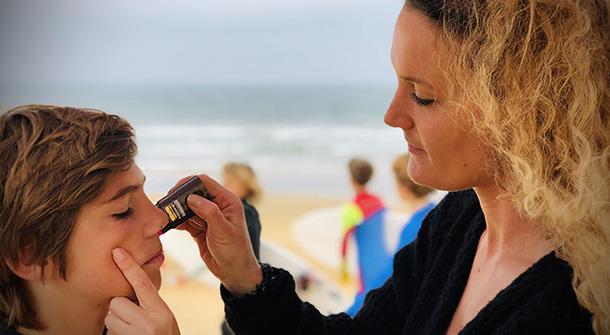 Femme qui applique du stick solaire sur les joues d'un garçon